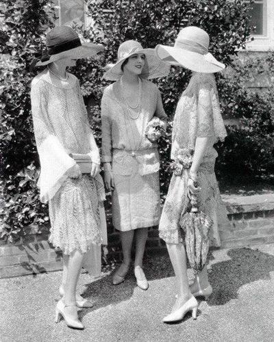 Три девушки одетые в стиле Гетсби, в платьях с заниженной талией и шляпах с широкими полями