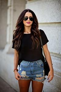 Девушка в шортах, черной футболке и с сумкой на плече