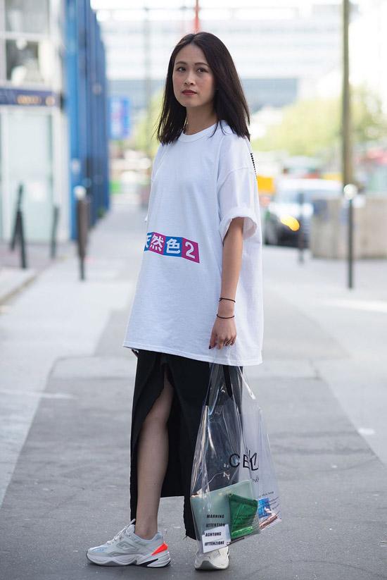 Девушка в белой футболке оверсайз и черной юбке макси с разрезом