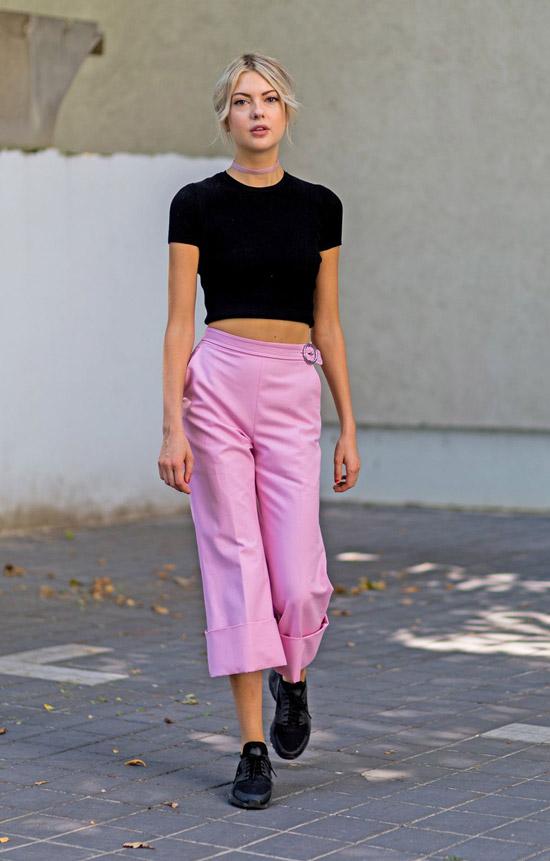 Девушка в черной укороченной футболке и розовых брюках с высокой талией