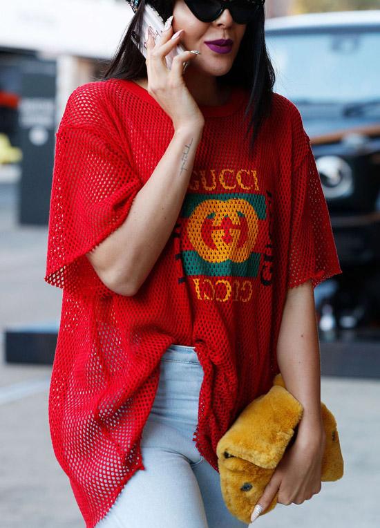 Девушка в красной футболке от Gucci и белых джинсах