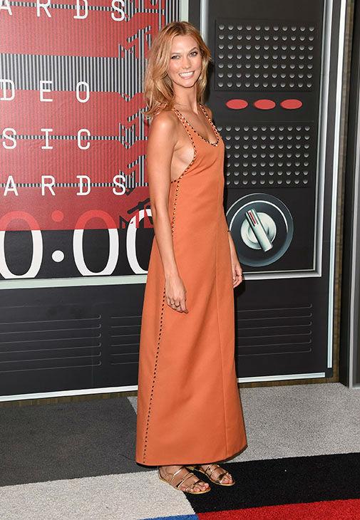 Модель Карли Клосс в длинном платье и сандалиях на низком ходу
