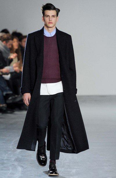 мужчина в черном пальто на подиуме