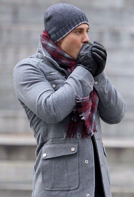 мужчина в сером пальто и красном шарфе
