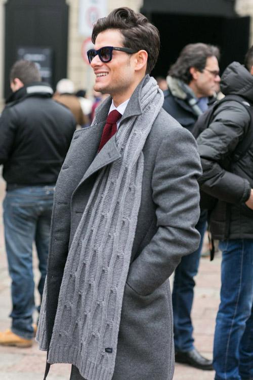 мужчинав сером пальто, шарфе и очках